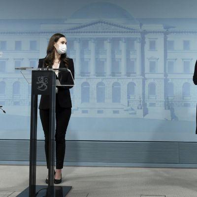 Statsminister Sanna Marin (till vänster) och arbetsminister Tuula Haatainen vid regeringens presskonferens. Båda har munskydd på sig och de står vid varsitt talarpodium.