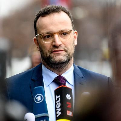 Tysklands hälsominister Jens Spahn intervjuas utomhus med mikrofoner framför sig..