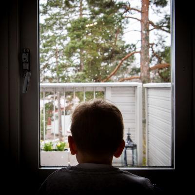 Lapsi katsoo ikkunasta ulos.