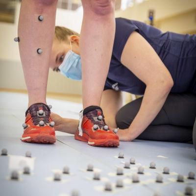 Heidi Jarske kiinnittää juoksijaan 3D antureita.