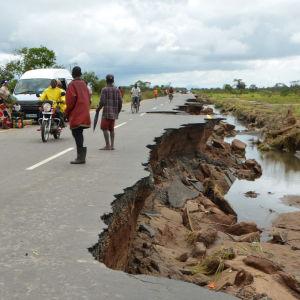 Människor går, cyklar och kör på en förfallen väg i Moçambique.