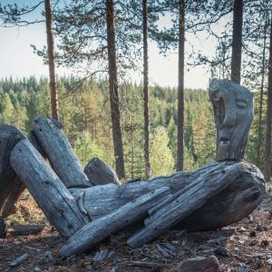 Puusta tehty veistos, maassa makaava hahmo, suussa harvat hampaat