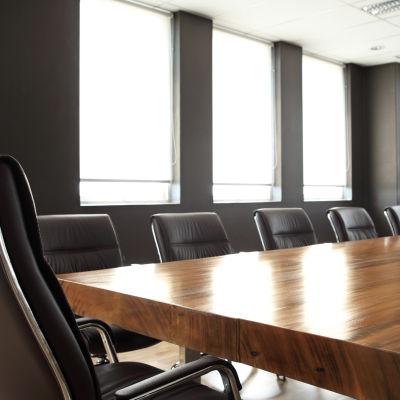 Ett tomt mötesrum med ett stort bord och flera stolar.