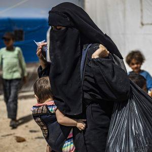 """En kvinna bär på sitt barn och sina tillhörigheter i lägret al-Hol i nordöstra Syrien den 3 juni 2019. Kurdiska myndigheter började sända hem cirka 800 syriska kvinnor och barn som tidigare i år evakuerades från IS """"kalifat""""."""