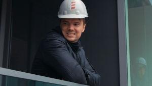 Bjarke Ingels tittar ut från en balkong med en vit bygghjälm på huvudet.