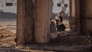 En kvinna håller ett barn i famnen och står vid en sönderbombad vägg.