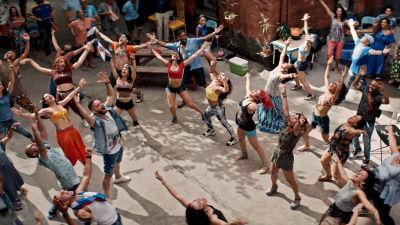 En massa människor dansar på en bakgård.