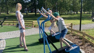 En kvinna med sommarklänning står med en liten flicka och en liten pojke som testar gymredskap