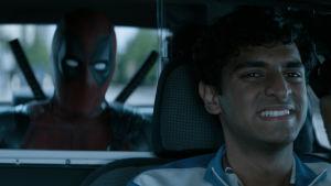 Taxichauffören Dopinder kör bil med Deadpool i baksätet.