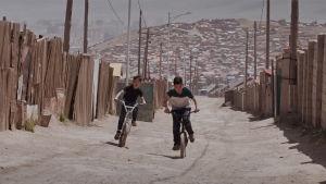 Två pojkar cyklar på en tom gata i en kåkstad.