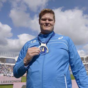 Olli-Pekka Karjalainen visar upp sitt EM-guld på Olympiastadion i Helsingfors.
