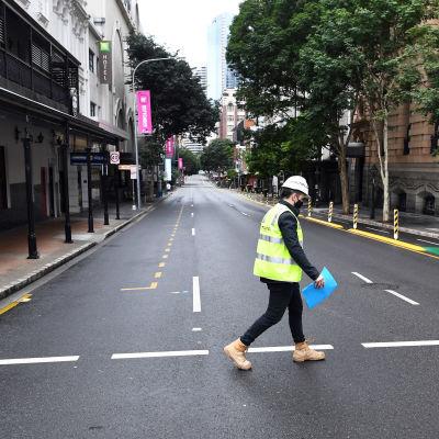 Kypärään ja suojaliiveihin pukeutunut työntekijä kävelee autiolla kadulla.