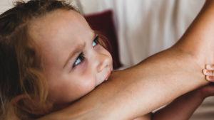 En liten flicka biter i en arm. Hon ser inte glad ut.