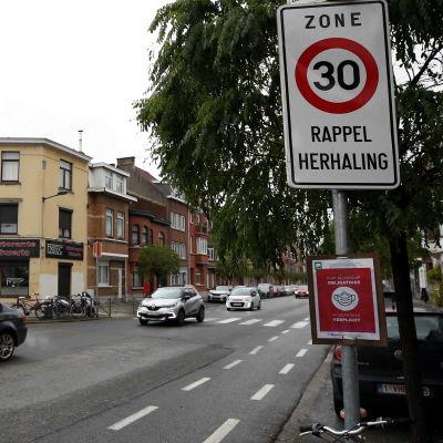En bil passerar en 30-skylt på en mindre väg.