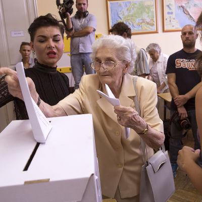 En väljare, omgiven av valarbetare och fotografer, lägger sin röst i en vallokal i Zagreb.