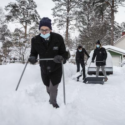Harlan Stevens ja kaksi muuta kirkon jäsentä kolaamassa lunta omakotitalon pihatiellä.