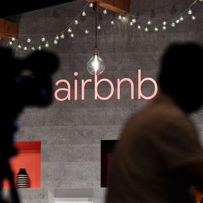 Aibnb:s logga på en vägg med skuggor av personer i fögrunden.