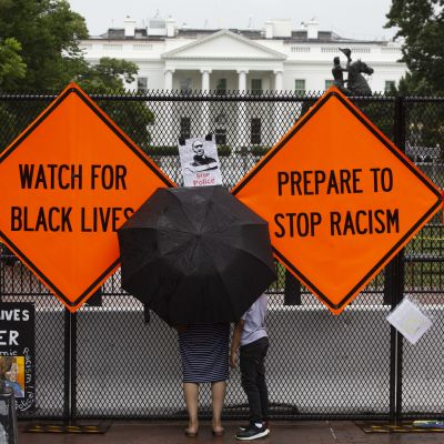 Black Lives Matter -mielenosoituskylttejä valkoisen talon aidassa