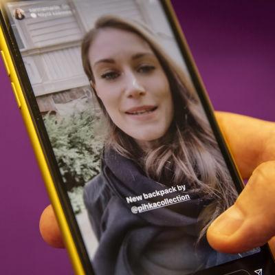Bild på en hand som håller i en telefon som visar Sanna Marin på hennes Instagramkonto.
