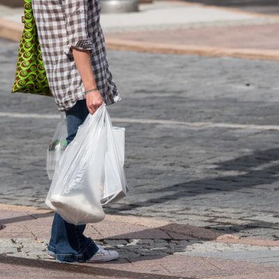 Nuori nainen ostoskassien kanssa.