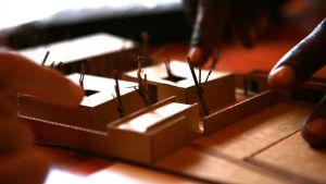 Fingrar pekar på miniatyrmodell av barnhemmet TunaHaki i Tanzania.
