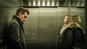 Sofia Karppi (Pihla Viitala) ja Sakari Nurmi (Lauri Tilkanen) seisovat hississä etäällä toisistaan. Karppi tuijottaa Nurmea, joka katsoo lattiaan.