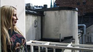 Meikkitaiteilija Piia Hiltunen seisoo parvekkeella vanhan kerrostalokorttelin sisäpihalla.