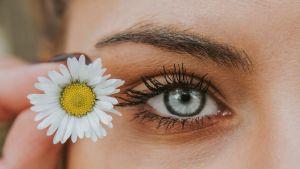 En närbild på en kvinnas halva ansikte och en liten blomma hon håller vid ögat.