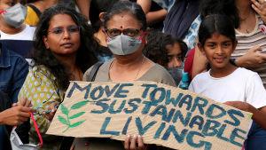Indisk kvinna med skylt. I bakgrunden syns flera andra människor.