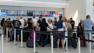 Människor står och köar vid en incheckningsdisk vid flygplatsen Stansted i Storbritannien.