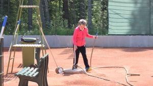 En kvinna på tennisplan. Hon spelar inte utan har just vattnat planen. Vattenslangen ligger på marken.