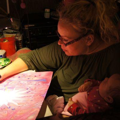 nainen piirtää vauva sylissään