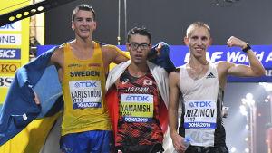 Perseus Karlström,Toshikazu Yamanishi och Vasiliy Mizinov står på rad efter målgång.