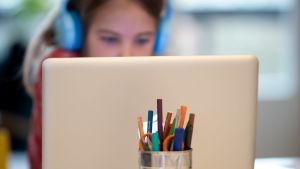 Skolelev deltar med fokuserad blick på datorskärm i distansundersvisning.