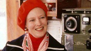 Margareeta II hymyilee merihenkinen asu yllään ja punainen myssy päässään.