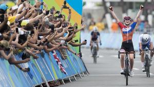 Damcyklist firar målgång i OS med sträckta händer.