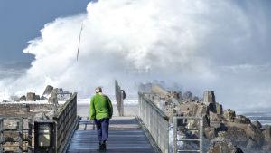 Stormen Knud slår upp stora vågor över en pir utanför Hanstholm, Danmark.