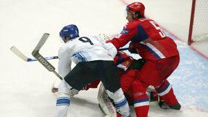 Mikko Koivu kämpar om pucken mot den ryska målvakten och en back