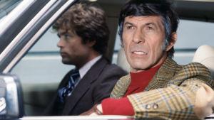 Mies katsoo ulos auton avoimesta ikkunasta ja nojaa siihen kädellään.