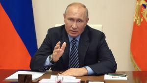 Rysslands president Vladimir Putin sitter vid ett sort skrivbord och pekar med hela handen. Den ryska federationens flagga står i bakgrunden.