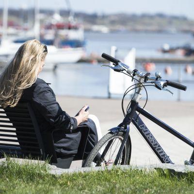 Kvinna sitter på en bänk och tittar på en mogiltelefon