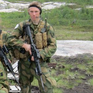 En man i militäruniform står på ett gräsbelagt fält. Han ser bestämt in i kameran. Han håller i ett stormgevär.