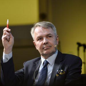 En gråhårig man i kostym parkerar med en penna i handen.