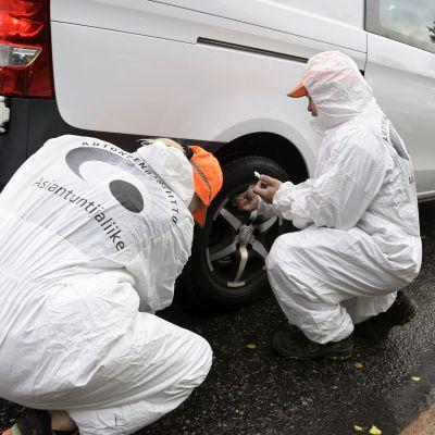 Två personer i vita overaller kontrollerar däcket på en paketbil.
