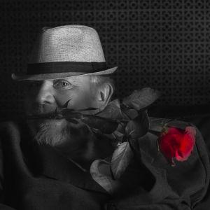 Svartvit bild på Mårten Holms ansikte, med vit hatt och en röd ros i munne.
