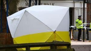 Den bänk där Sergej och Julia Skripal hittades förra veckans söndag stod fortfarande tältbeklädd, avspärrad och bevakad på tisdagen.