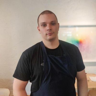 Krögare Kim Mikkola syns i förgrunden klädd i förkläde och t-skjorta. I bakgrunden syns en vit vägg med en färggrann tavla.