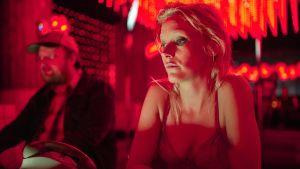 Laura Birn istuu punaisessa valossa baaritiskillä. Kuva lyhytelokuvasta Kaksi ruumista rannalla.