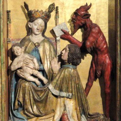 Keskiaikainen veistos kirkossa. Kuvattuna Neitsyt Maria Jeesus-lapsen kanssa, joku rukoilee polvillaan. Piru tarjoaa kirjaa (?)
