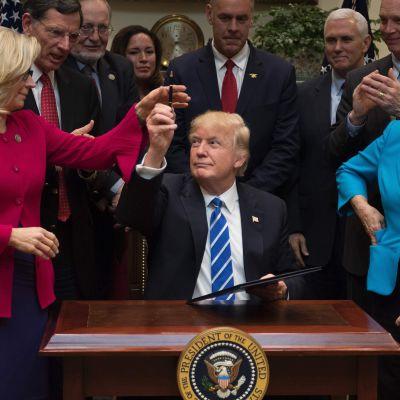 Donald Trump, omgiven av republikanska politiker, undertecknar resolutioner i Vita huset 27.3.2017